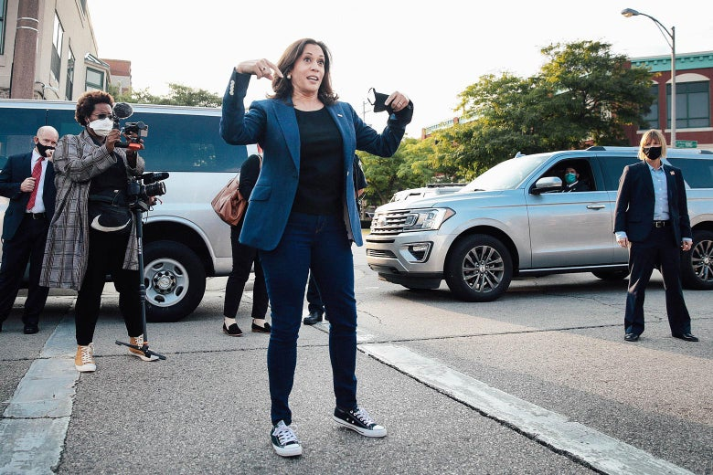Harris, wearing a business casual outfit and Converse sneakers, stands on the pavement addressing supporters