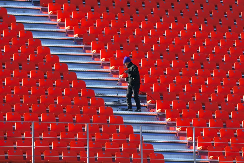 A lone worker sets up a cable at the Olympic Stadium in Pyeongchang, surrounded by a sea of empty, red seats.