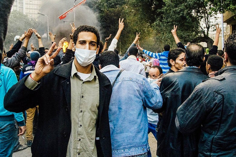 A man in a face mask makes a peace sign in a crowd.