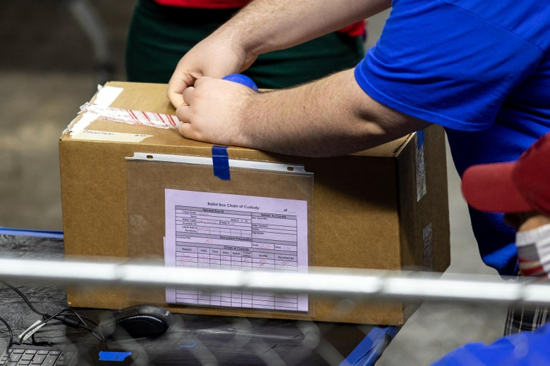 A contractor working for Cyber Ninjas opens a box of Arizona ballots cast in the 2020 election.