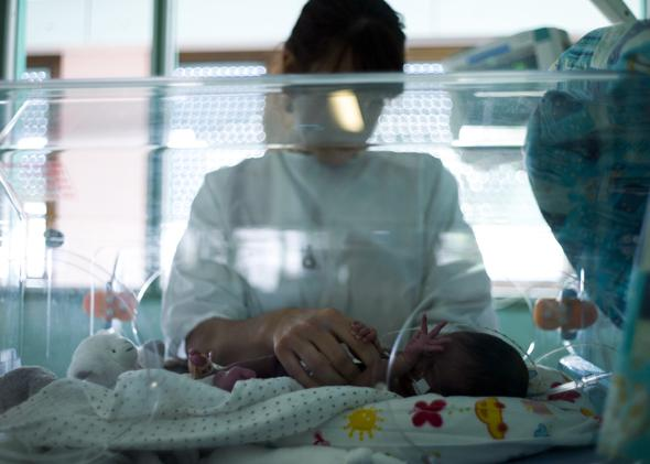 A nurse takes care of a premature baby at the maternity ward.