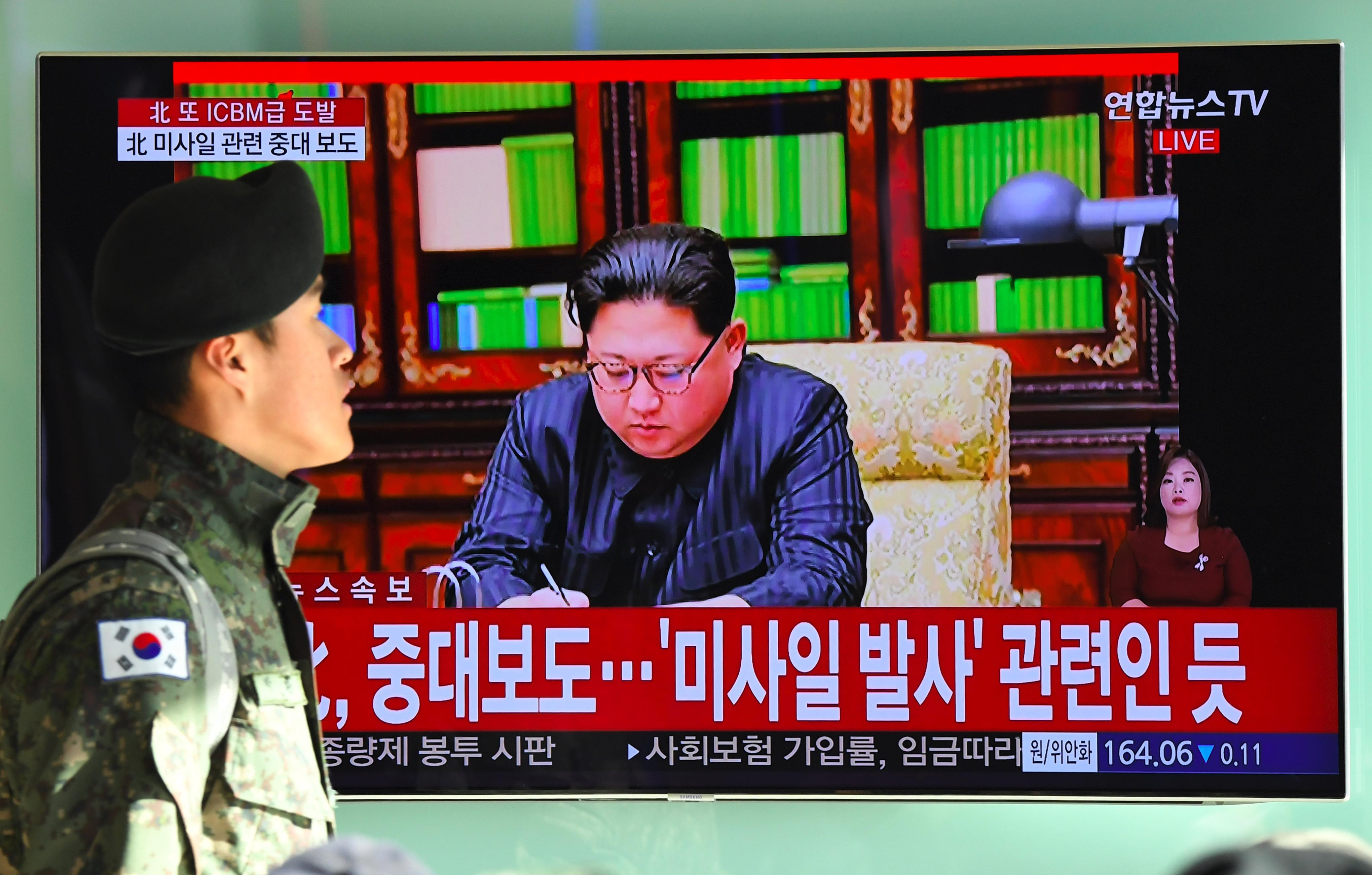 A South Korean soldier walks past a television news screen showing North Korean leader Kim Jong-Un approving the country's new ICBM test, at a railway station in Seoul on November 29, 2017         Nuclear-armed North Korea said on November 29 it had successfully tested a new intercontinental ballistic missile that put 'all of the US continent' within its range.  / AFP PHOTO / JUNG Yeon-Je        (Photo credit should read JUNG YEON-JE/AFP/Getty Images)