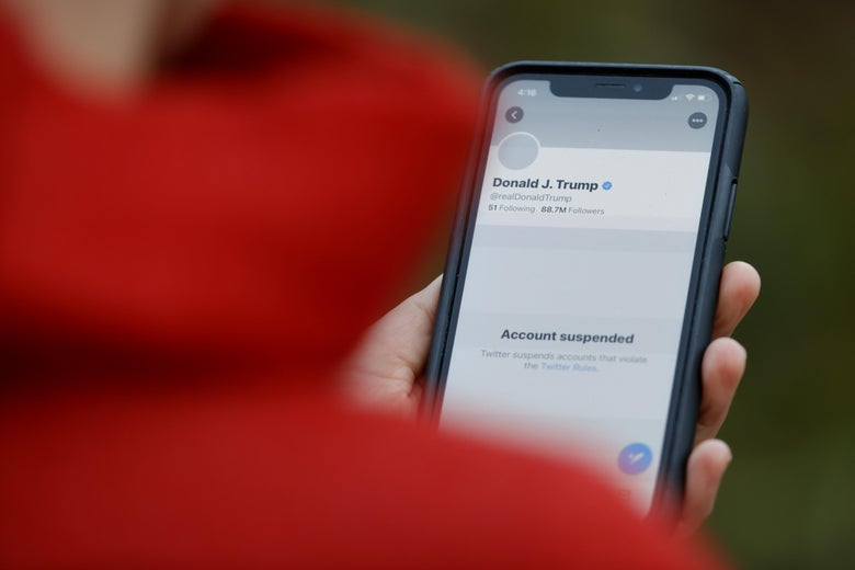 Person in a red hoodie seen from the back, holding an iPhone open to the suspended Twitter account of U.S. President Donald Trump