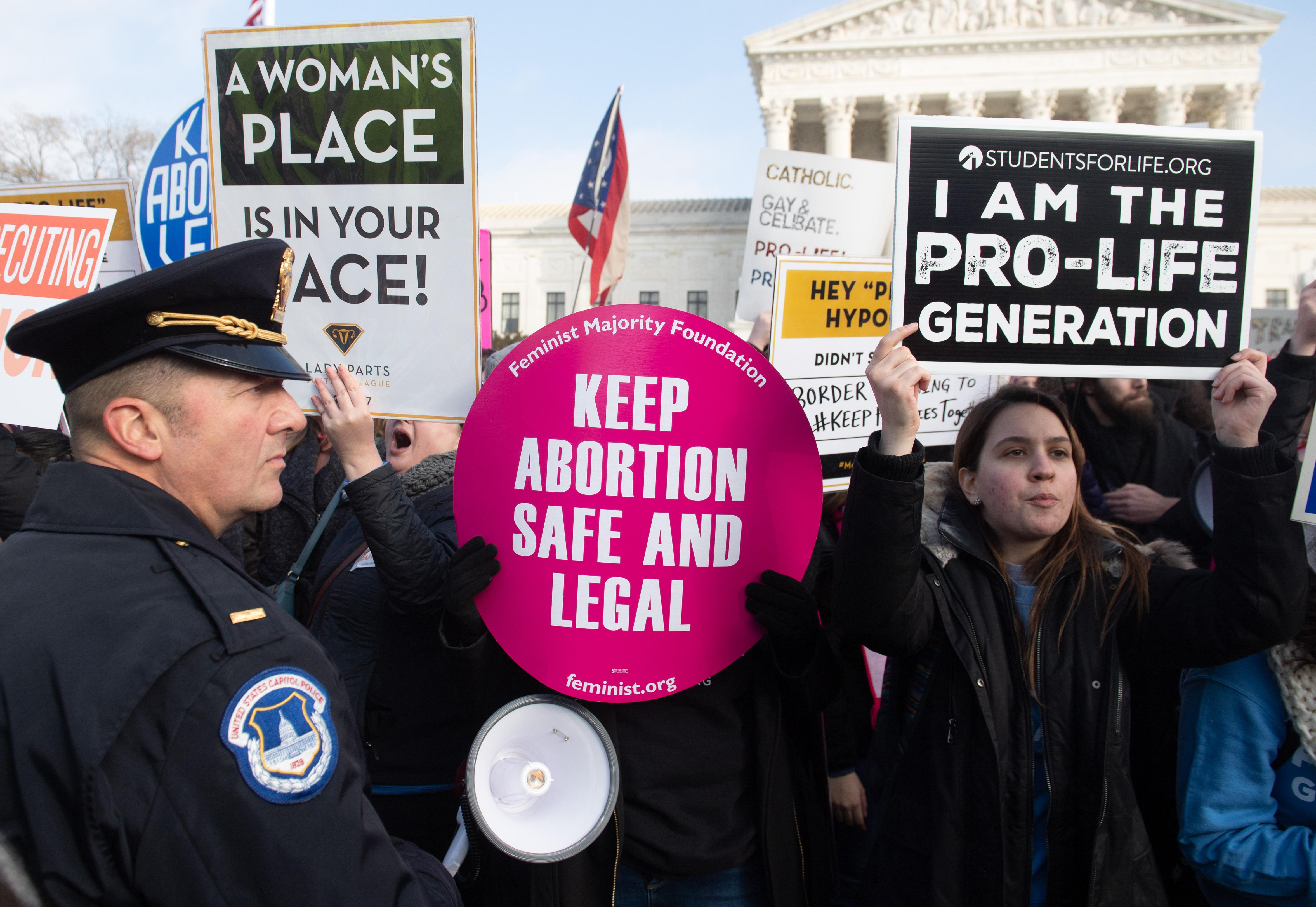 Pro-choice activists hold signs in response to the anti-abortion March for Life outside the U.S. Supreme Court in Washington, D.C., on January 18, 2019.