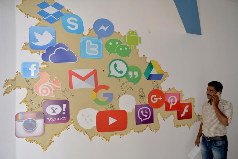 An visitor passes a mural depicting various social media in Bangalore.