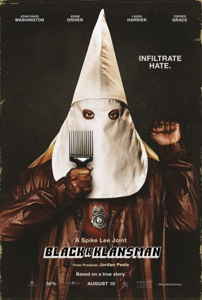 A poster for BlacKkKlansman: John David Washington, who is black, stands with a white hood over his head and a police badge around his neck. His hand is raised in a fist.