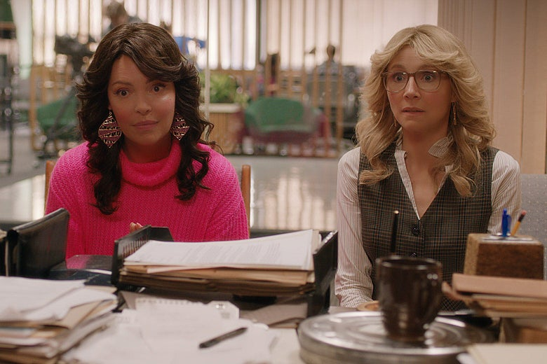 Katherine Heigl and Sarah Chalke sitting at a desk, looking bewildered, with Farrah Fawcett–style hair