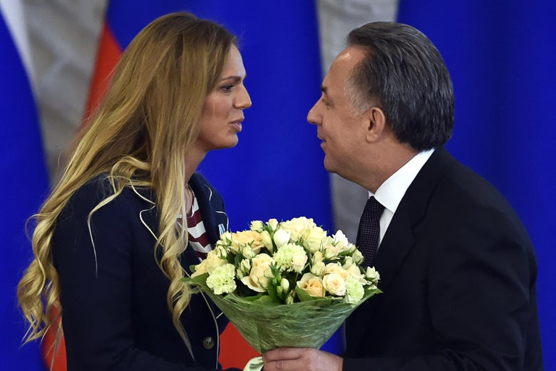 A woman on the left in formal attire receives a bouquet of flowers from an older man on the right wearing a suit.