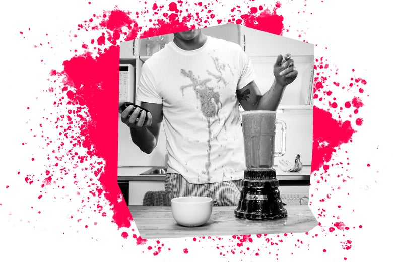 A man in front of an open, overflowing blender, with food stains on his shirt.