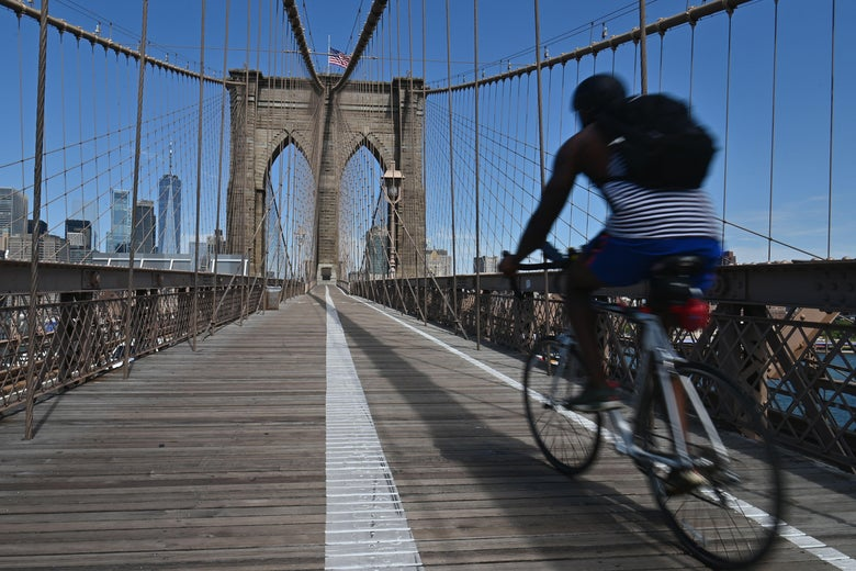 People ride bikes to commute over the Brooklyn Bridge amid the coronavirus pandemic on August 3, 2020 in New York City. (Photo by Angela Weiss / AFP) (Photo by ANGELA WEISS/AFP via Getty Images)