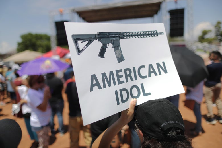 A demonstrator holds a sign depicting an assault rifle at a protest against President Trump's visit, following a mass shooting which left at least 22 people dead, on August 7, 2019 in El Paso, Texas.