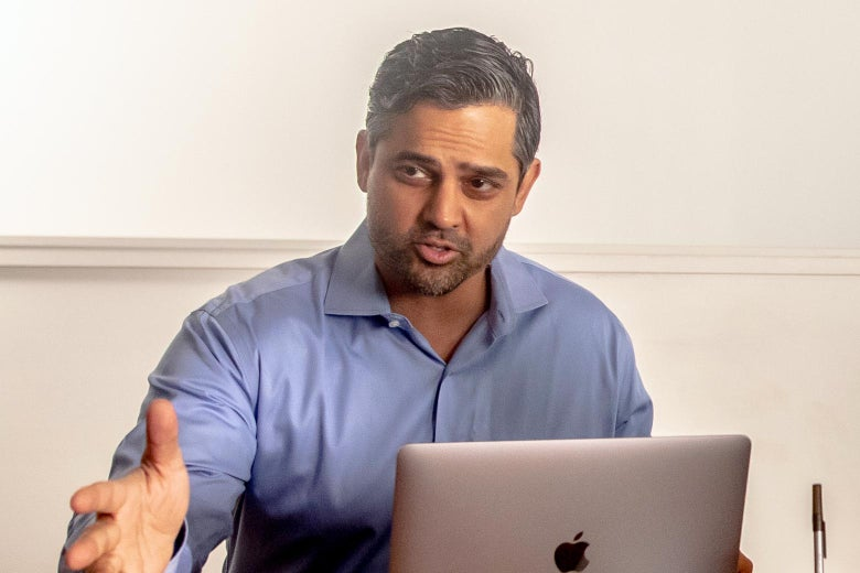 Sri Preston Kulkarni sits in front of a Macbook while talking and gesturing with his hands.