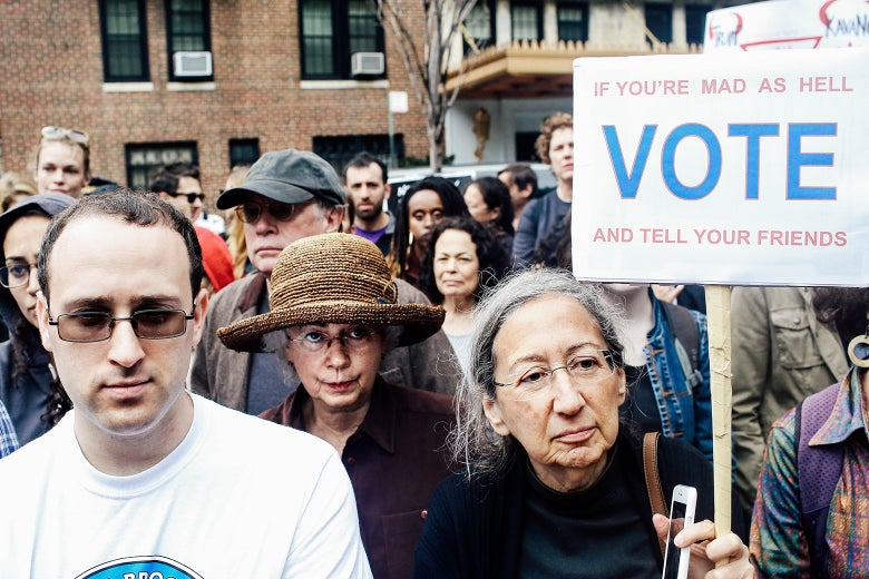 """People gather in protest against Brett Kavanaugh. One woman holds a sign reading """"IF YOU'RE MAD AS HELL, VOTE AND TELL YOUR FRIENDS."""""""