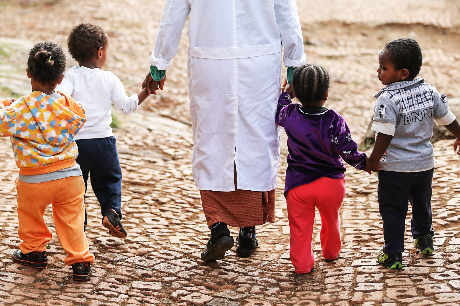 A woman walks with orphans at the AGOHELD orphanage, hospital, training center and school on March 19, 2013 in Addis Ababa, Ethiopia.