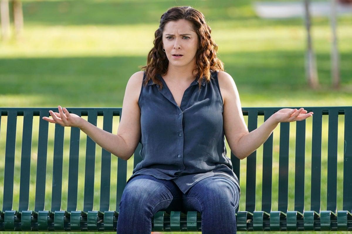 Rachel Bloom sits on a park bench, shrugging her shoulders.