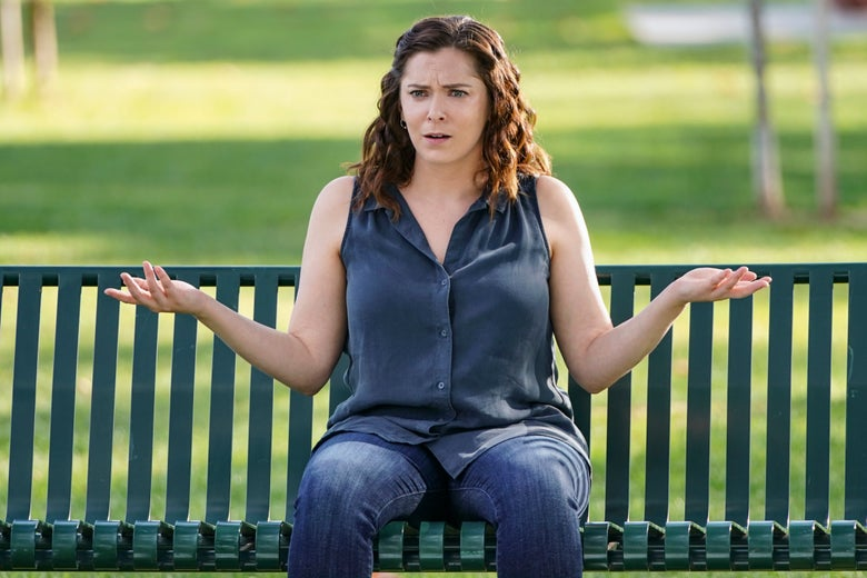 Rachel Bloom sits on a park bench, shrugging her shoulders.