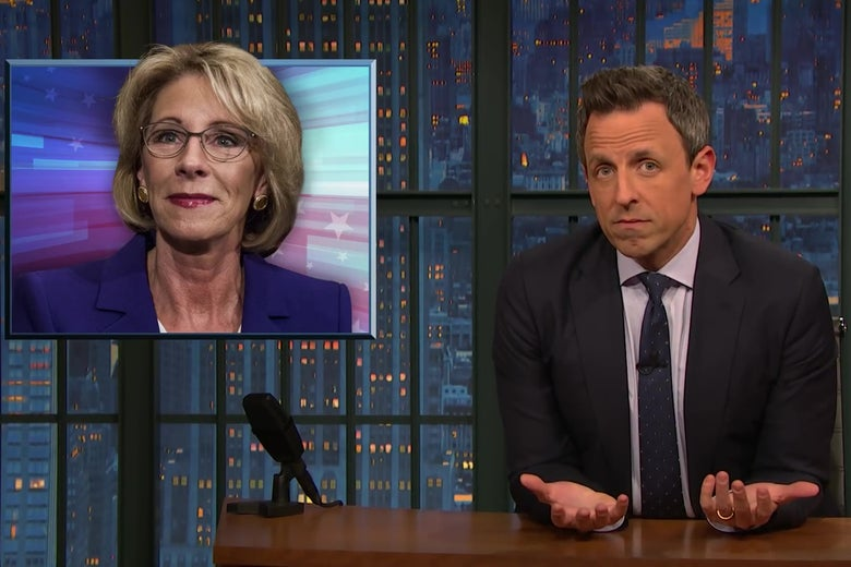 Seth Meyers at an anchor desk, in front of a picture of Betsy DeVos.