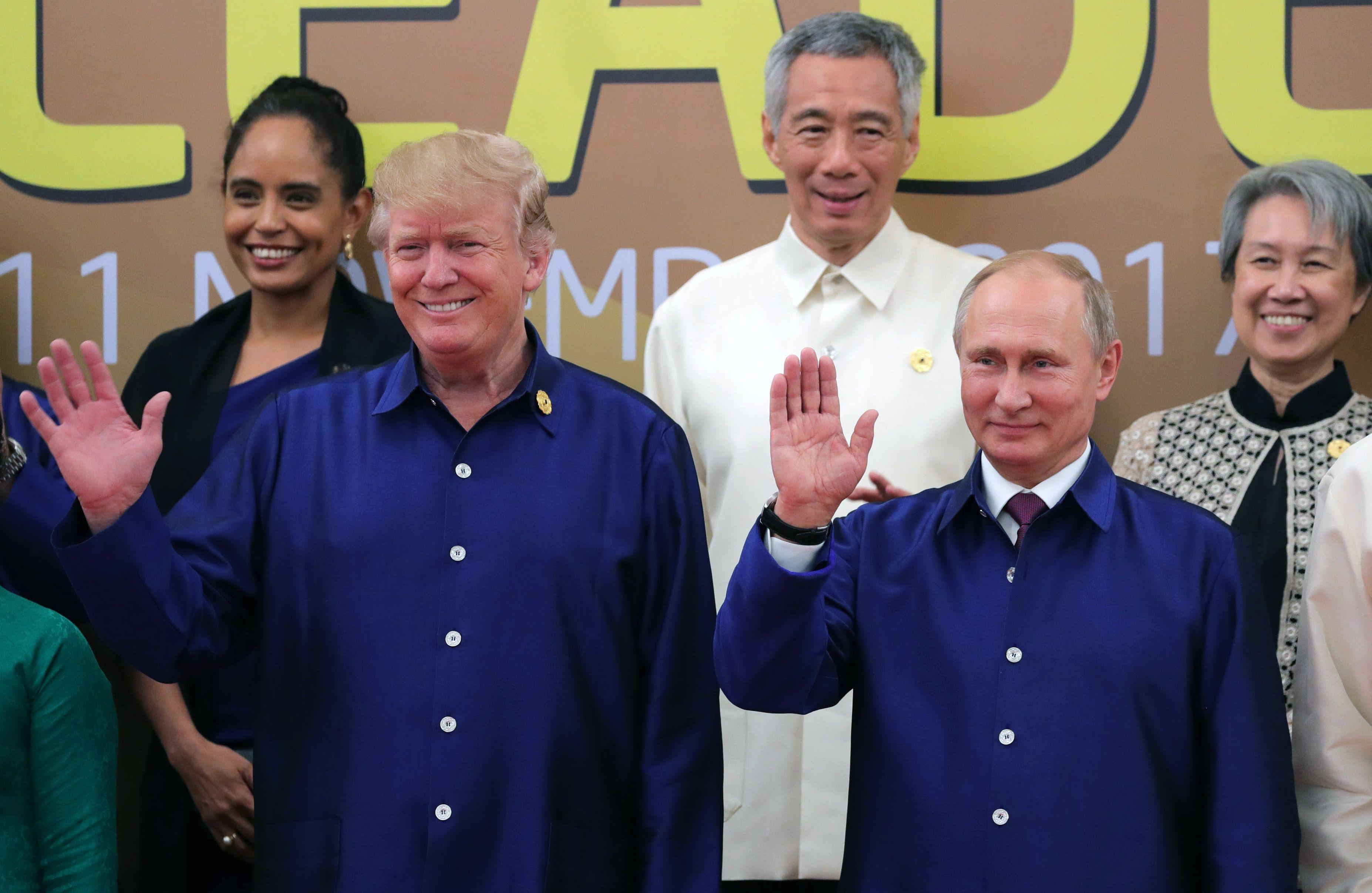 US President Donald Trump (L) and Russia's President Vladimir Putin (R) wave as they pose for a group photo ahead of the Asia-Pacific Economic Cooperation (APEC) Summit leaders gala dinner in the central Vietnamese city of Danang on November 10, 2017. / AFP PHOTO / SPUTNIK / Mikhail KLIMENTYEV        (Photo credit should read MIKHAIL KLIMENTYEV/AFP/Getty Images)