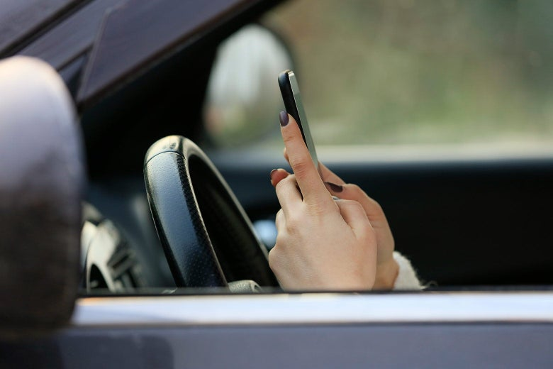 A woman texting while driving a car.