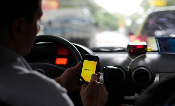 A taxi driver checks an app on his smartphone in Rio de Janeiro April 15, 2013.
