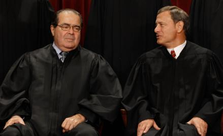 U.S. Supreme Court Associate Justice Antonin Scalia (L) and Chief Justice John Roberts talk while posing for photographs in the East Conference Room at the Supreme Court building October 8, 2010 in Washington, DC.