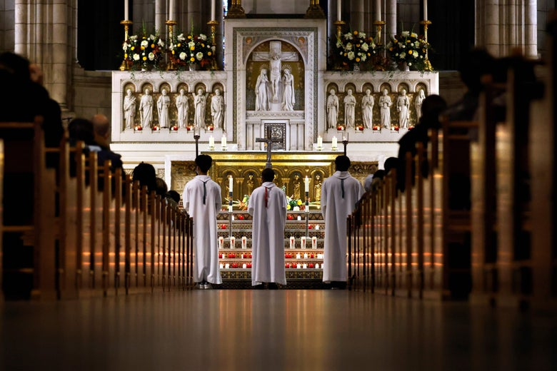 Three priests stand at an altar, as seen from behind. One of them carries a crucifix.