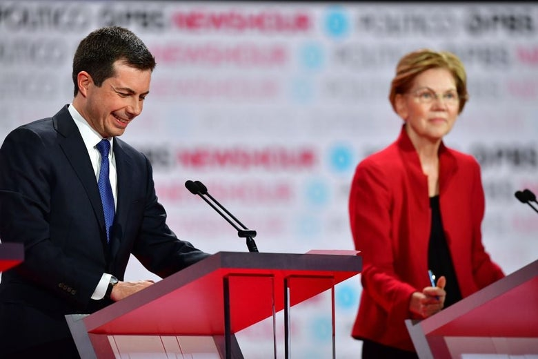 Buttigieg laughs while looking down at his lectern while Warren is seen in the background.