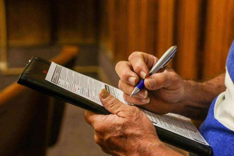 Man filling out a voter registration form in pen