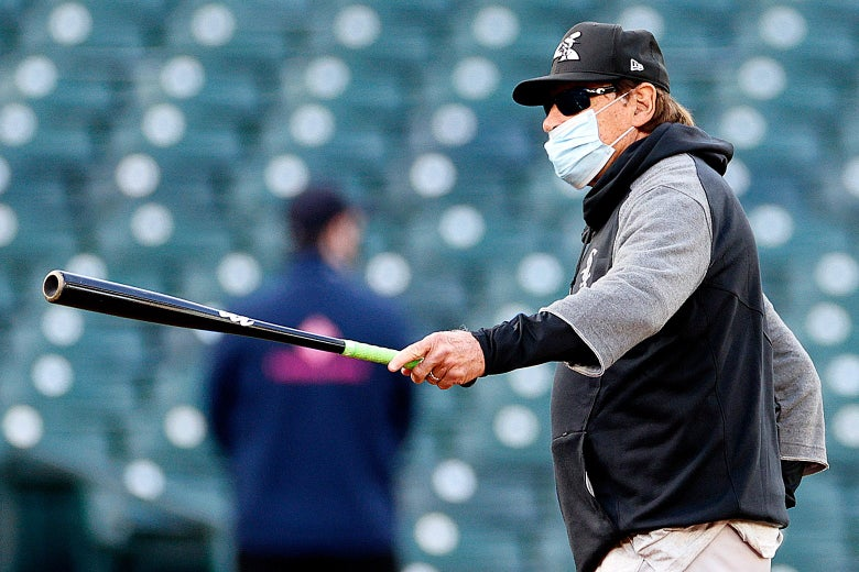Tony La Russa holds out a bat in one hand. He is wearing a face mask that doesn't cover his nose.