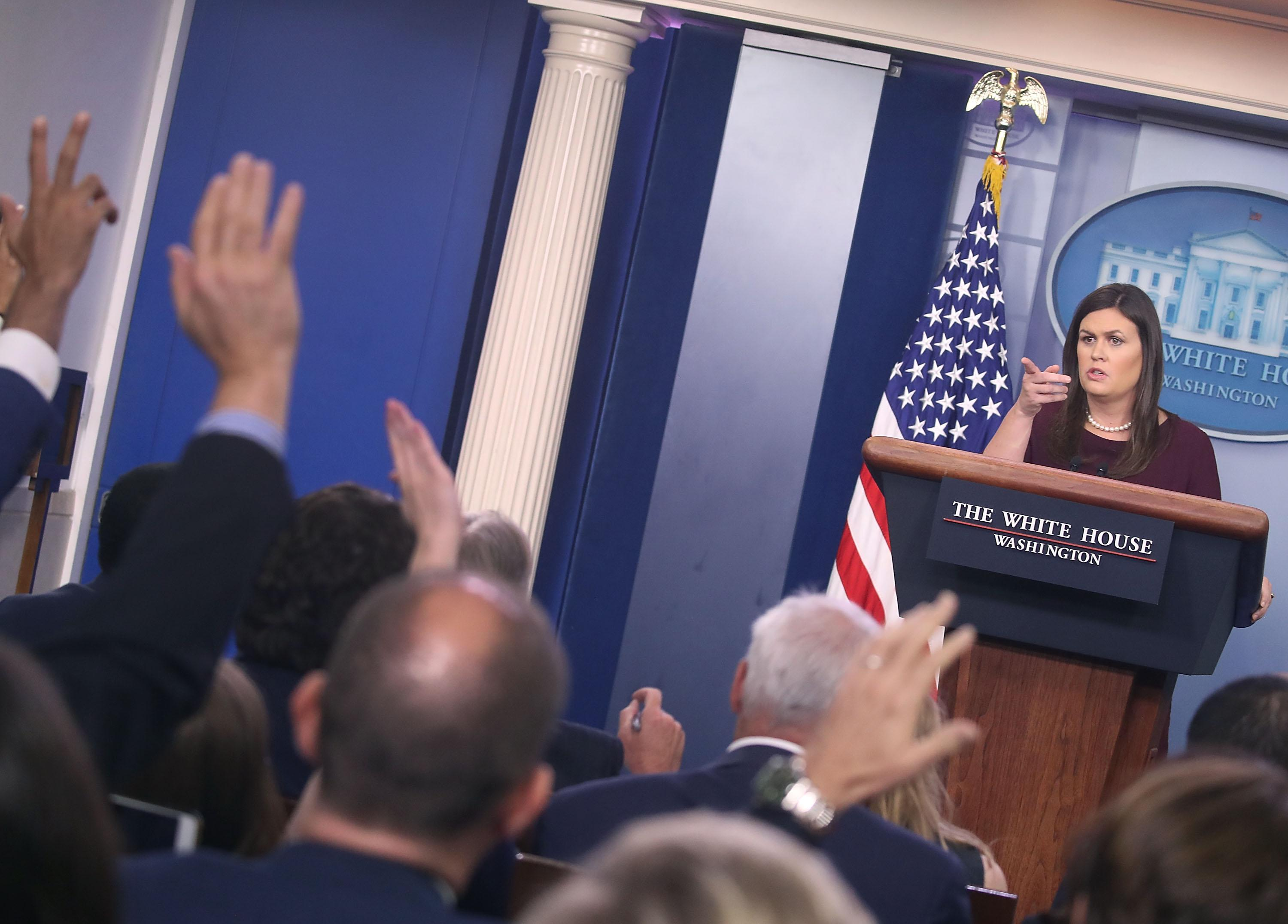 Sarah Huckabee Sanders points to reporters from behind the podium in the Briefing Room.