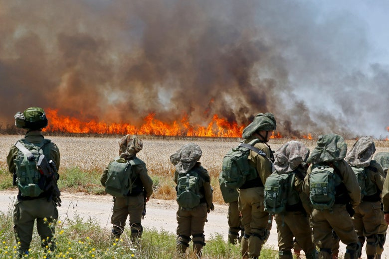 Israeli soldiers walk amid smoke from a fire in a wheat field.