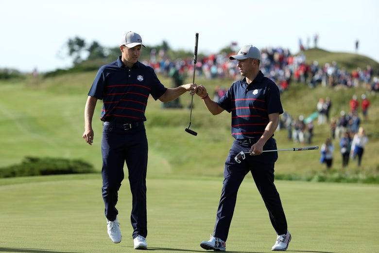 Jordan Spieth and Justin Thomas bump fists on the green of a golf course.