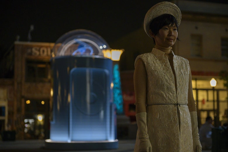 Watchmen's Lady Trieu stands in the town square of Tulsa, a glowing booth behind her.
