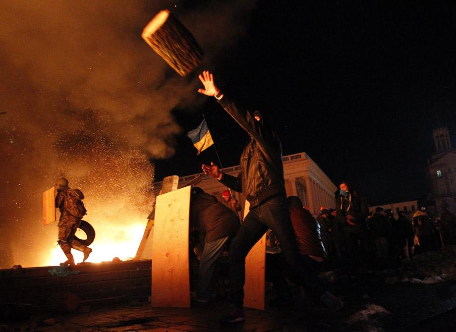 A protester throws a log during clashes with riot police at Independence Square in Kiev