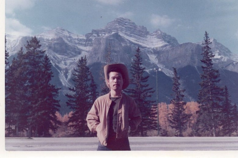 A young Japanese man wears a hat with a broad brim as he stands by the side of the road in front of a mountain range.