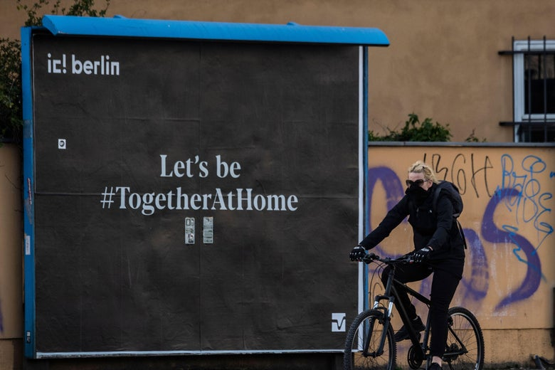 """A woman wearing a face cover cycles past a poster reading: """"Let's be together at home."""""""
