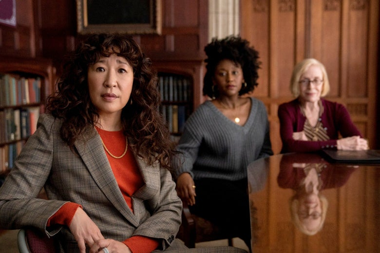 The three women sit at a table in a room lined with bookshelves.