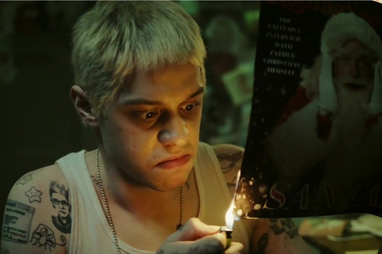 Pete Davidson, with his hair died blonde like Eminem, sets a photograph of Santa Claus on fire.