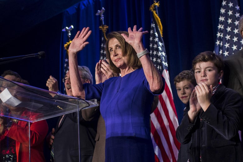 Nancy Pelosi raises her hands from behind a podium.