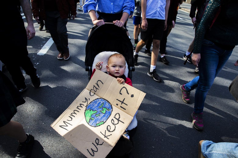 "A baby in a stroller holds a sign with a drawing of Earth. The sign reads, ""Mummy, can we keep it?"""