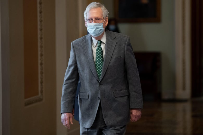 Mitch McConnell, wearing a medical mask, walks down a hallway at the Capitol