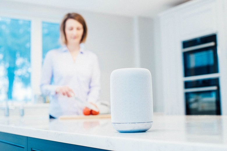 A device that looks like an Apple HomePod rests on a kitchen counter while a woman prepares food in the background.