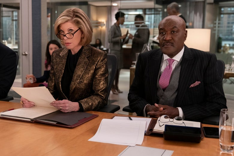 Christine Baranski and Delroy Lindo sit on one side of a conference table. Baranski cocks an eyebrow.