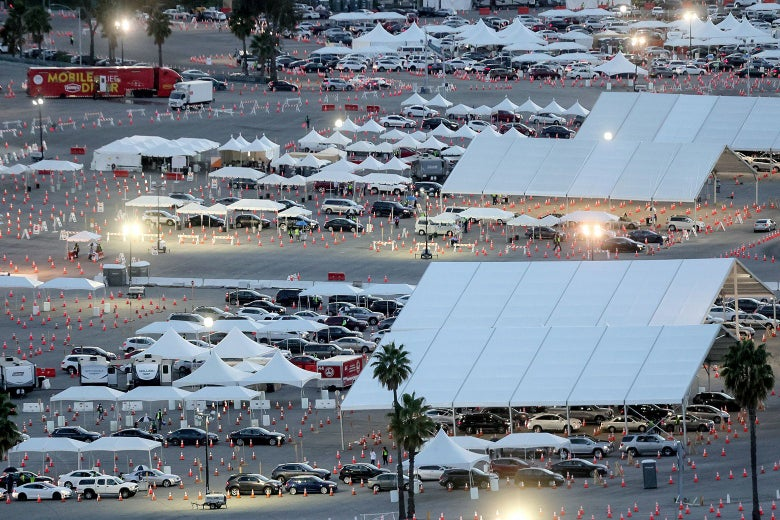 A parking lot full of cars under tents and in lanes marked off by traffic cones