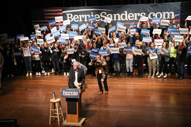 Bernie Sanders speaks at a podium, with a crowd of his supporters standing behind him onstage.