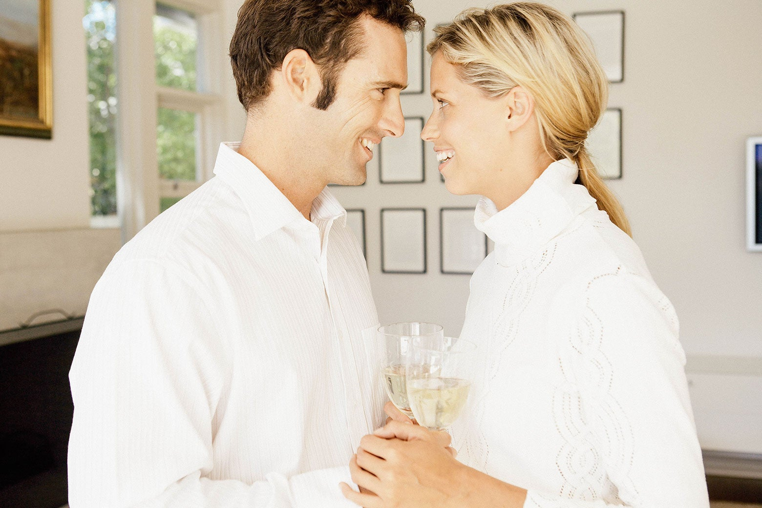 A man and a woman dressed all in white and holding a light-colored beverage grin into each other's faces.