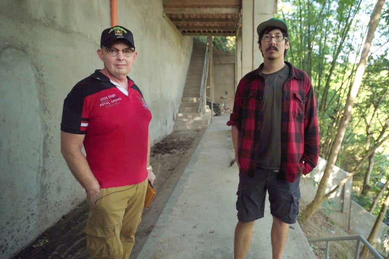 Jim and Ron Watkins look at the camera as they stand on a concrete walkway on a pig farm.