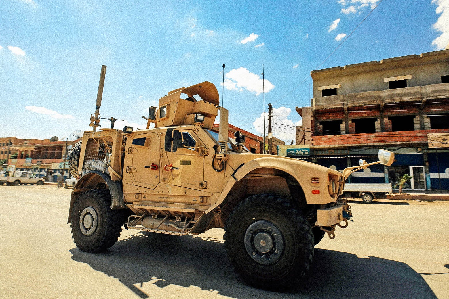 Vehicles of the U.S.-led coalition battling the Islamic State group patrol the town of Rmelane.