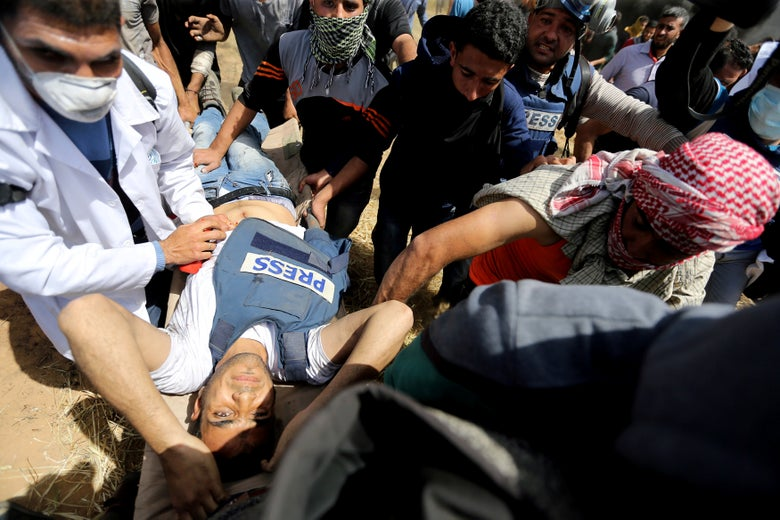 Mortally wounded Palestinian journalist Yasser Murtaja, 31, is evacuated during clashes with Israeli troops at the Israel-Gaza border, in the southern Gaza Strip on April 6, 2018.