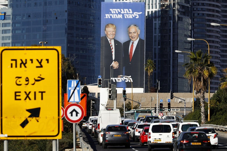 A picture taken on February 3, 2019 in Tel Aviv shows a giant election billboard of Israeli Prime Minister Benjamin Netanyahu and U.S. President Donald Trump shaking hands.